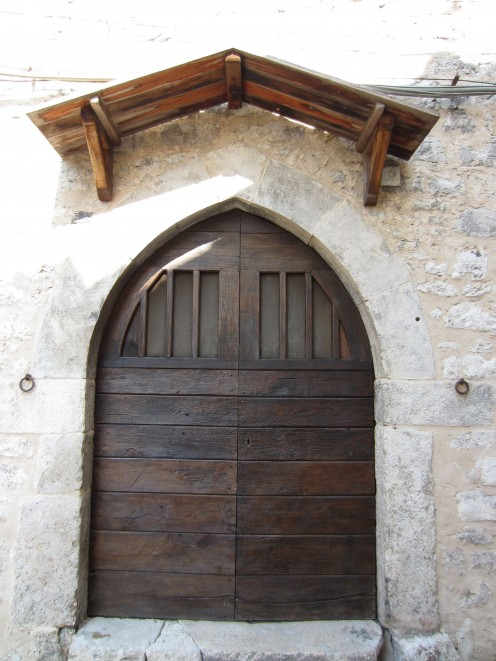 Wooden door - the main entrance to one of the old buildings in the center. Amaseno, Italy