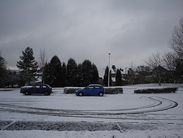 A parking lot after a snow. The cars, the Vauxhall Corsa is made by GMC. Fun cars to drive, all be it a little cramped. I learned to drive manual transmissions in the UK. That was a lot of fun!