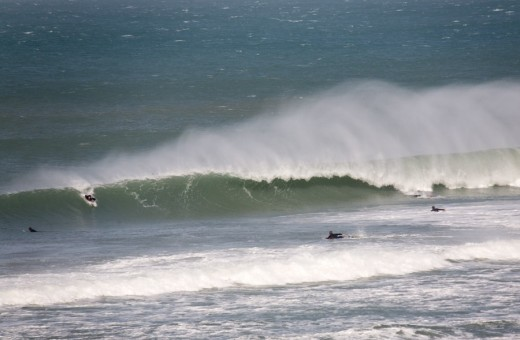 Surfer paddles into a wave at Porthmeor beach