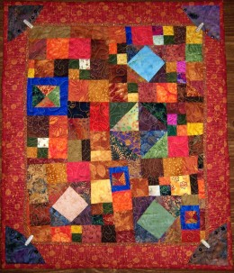 This scrap quilt uses mainly warm color fabrics, with a few cool fabrics for contrast.