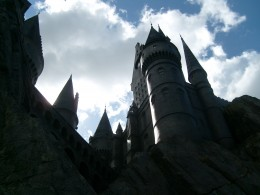 The towers of Hogwarts loom over the muggles in line.