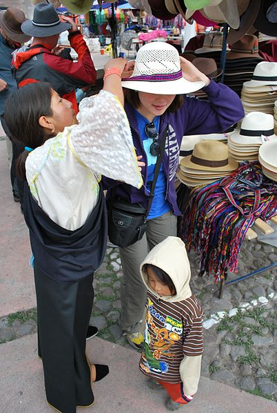 An Otavalo woman helps a tourists try on a hat.