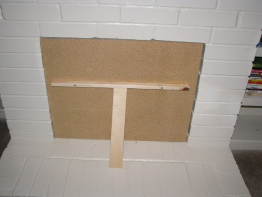 Simple fireplace insert wedges in place without screws or anchors.