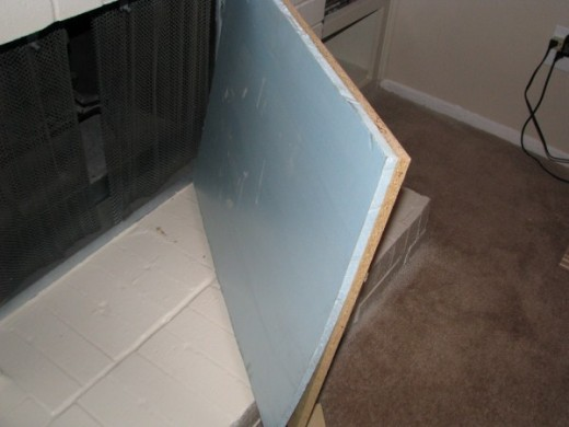 Styrofoam backing glued to the wood helps insulate the fireplace insert.