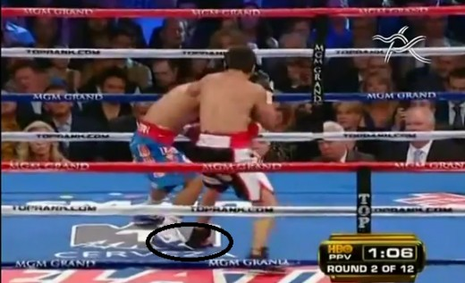 The image shows that Marquez in black trunks is seen stepping on Pacquiao's foot, an ingenious way of neutralizing the speed  of an opponent