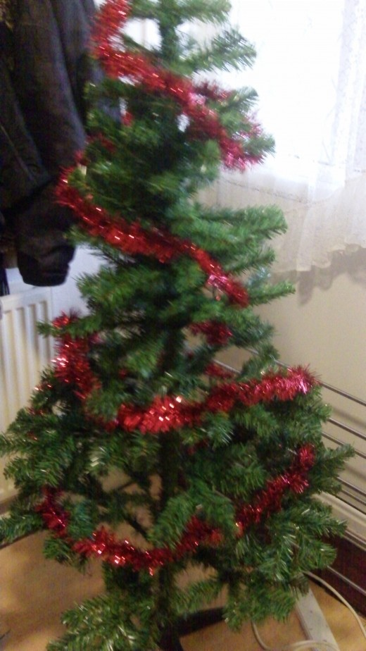 Tadaaaaa! One line of tinsel has been wrapped around the tree, we can now add another one....