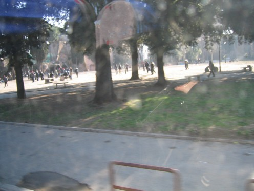 This picture was taken inside the bus.  It is looking out at a nearby park where people are meeting up for the Peace Rally.