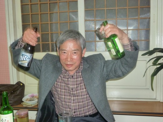 This is my principal holding up a beer bottle and a bottle of soju (rice liquor).