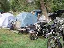 WHAT A PARDOX. A FEW TENTS AND A HIGH-PERFORMANCE MOTORCYCLE OR TWO. NOW THIS IS ROUGHING IT.