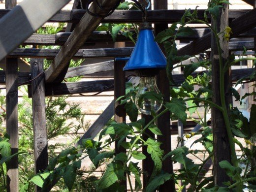 A bright blue light fixture hanging in the garden.