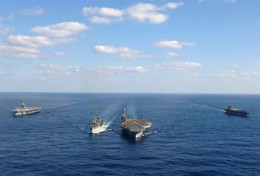 Three carriers and a re-supply ship manuevering in close quarters.