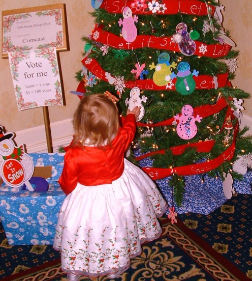 A little girl at the Festival of Trees at Dover Downs Hotel can't resist touching a snow man ornament on a tree donated and decorated by Dover's Girl Scout Troop 1090 and sponsored by Comcast.