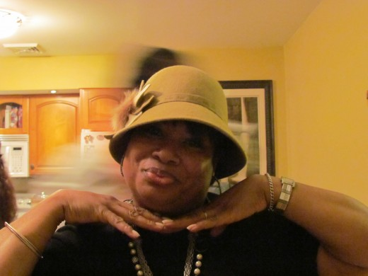 Anita Broady, served as host for Girl's Night Out With the Mad Hatter. She also models this gold colored brim.