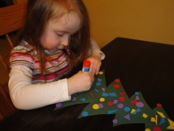 I helped her cut out circles and a star.  She glued them on and then cut out her own little shapes.