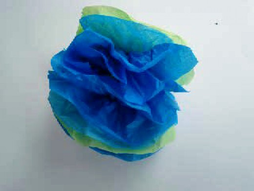 Fluff out the tissue for forming a paper flower.