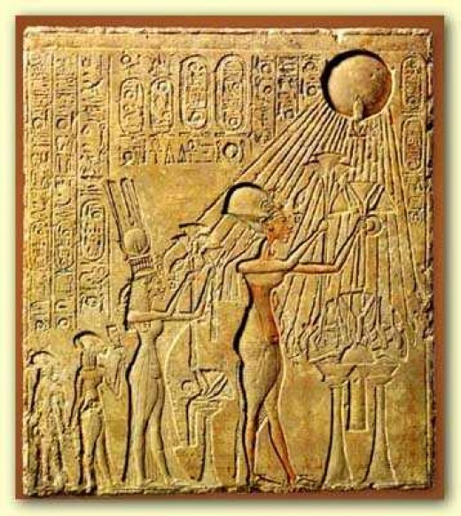The Aten (sun disc) pouring rays on Pharaoh and family.