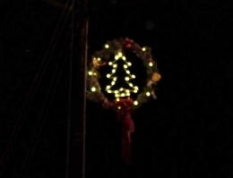 Another town's wreathed lights around Christmas trees.