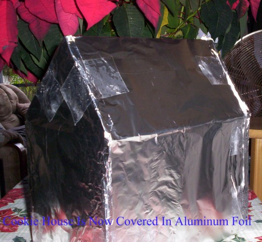 The cardboard Gingerbread House is wrapped in Aluminum Foil