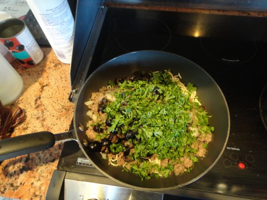 Adding the olives, parsley, salt, and pepper with the pasta and meat mixture