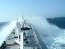 A ship's hull endures harsh conditions at sea, as illustrated by this reefer ship in bad weather.