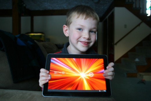 My son with our new tablet computer. The screen is large and has a bright display with sharp colors.
