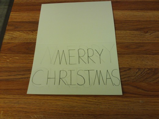 "Write the words ""Merry Christmas"" in printed text on the front of the card."