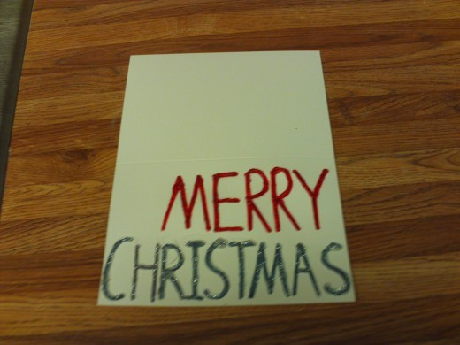 "I used the glitter paint to trace over the grey text of ""Christmas""."