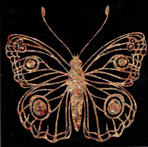 Gilded butterfly on black ceramic tile