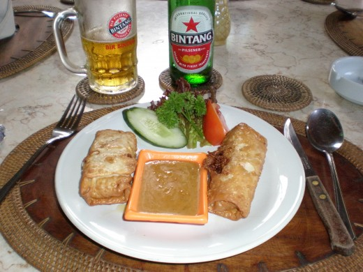"Indonesian food, authentic ""Lumpia"" with spicy peanut sauce accompanied by a Indonesian ""Bintang"" blond beer. Ubud chilled-out restaurant. Bali, Inonesia."
