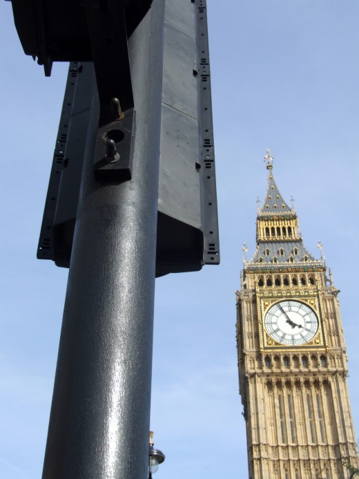 A image of the houses of Parliament sometimes nicknamed Big Ben which is located in central London. Also their is a traffic light in the image giving a typical London City view.