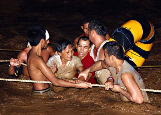 An old woman groping for ropes as fellow residents rescue her from the muddy flash flood.