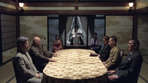 At the table are the six men hunting Izo.  Before then is the god-like emperor, the woman and man to his side wear traditional garb.