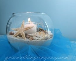 Beach centerpiece made with sand, shells a candle and blue tulle.