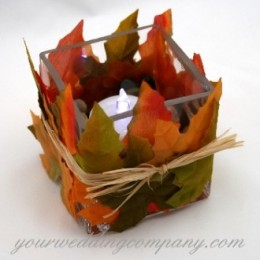 This autumn table accent is made with silk fall leaves and a square glass tealight holder.