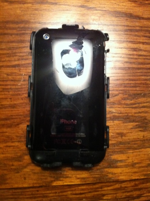 The back of the iPhone 3G / 3GS sitting in the front half of the OtterBox Defender's hard plastic case with the back half of the plastic case removed.