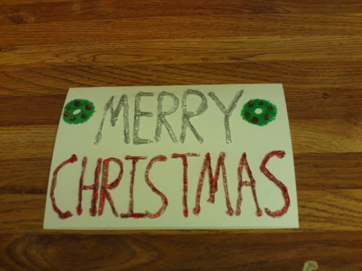 I used silver and red glitter glue to decorate the Merry Christmas message on the front of the card.
