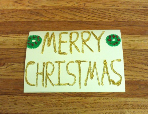 Gold glitter glue is used to glaze over the words Merry Christmas.