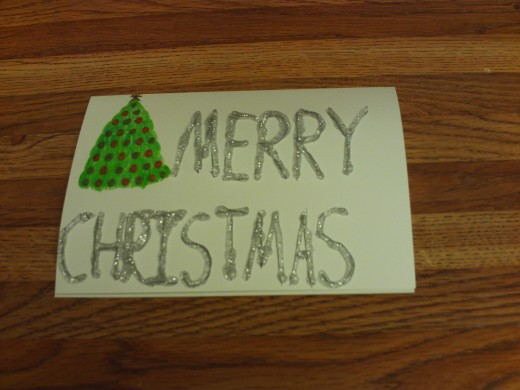 The Christmas text is glazed with silver glitter glue.