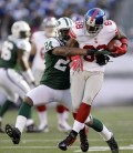 New York Jets' Darrelle Revis, left, tries to  Dec. 24, 2011, in East Rutherford, N.J. (AP Photo/Julio Cortez)
