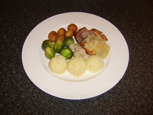 A slice of stuffed roast belly pork, served with roasted potatoes, Brussels sprouts, potato and parsnip mash and apple sauce