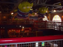 Inside Pizza Planet are giant Little Green Men from Toy Story overlooking the arcade area below