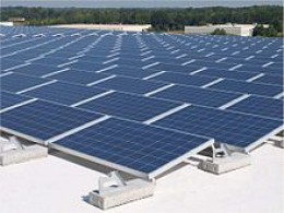 A roof mounted solar panel system installed using flat roof precast concrete ballasted footings.