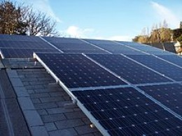 A roof mounted solar panel system installed on a sloped roof using pole mounts and rails.