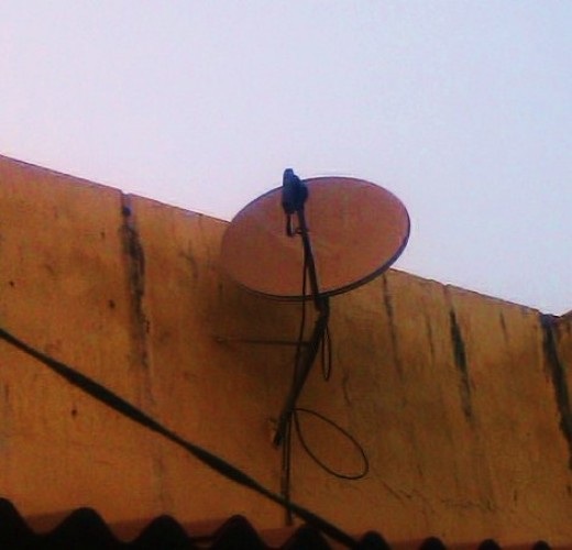small dish antenna directing towards the satellite to receive the signal. The weak signal received is amplified and given to set top box through cables.
