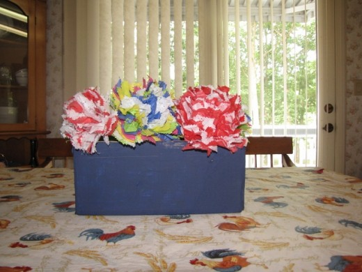 We used this finished centerpiece to decorate the buffet table at a surprise party for my mother-in-law, Lil. We also painted empty soup cans blue and placed miniature tissue flower arrangements in them.