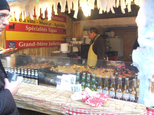 Essential to beer and gluwein consumption is stand-up eating and people-watching at the Christmas Market in Brussels; as we stop at the Spanish Tapas stand.