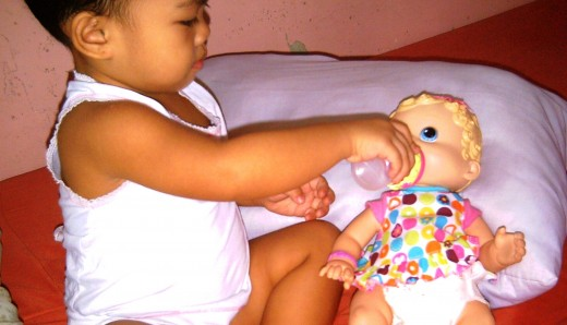 Baby Pauleen bottle-feeding her doll