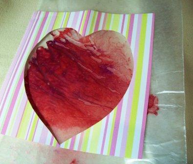 Unfold and using craft glue, center heart over your favorite part of the melted wax.