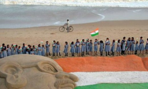 On the Indian Independence day a sculpture showing Mahatma Gandhi and the Indian national flag at the Puri beach.