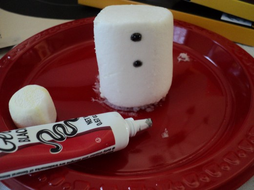 Use black tubed frosting gel to make two coal buttons on the side of the jumbo sized marshmallow.